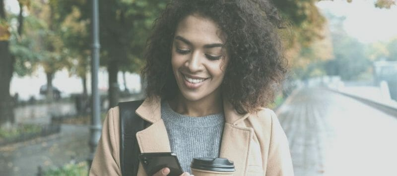 Black woman holding phone smiling wearing brown jacket smiling on a rainy day